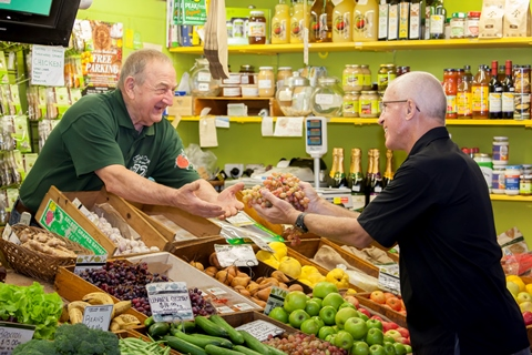 Mature age worker in fruit and vegetable shop serving a client