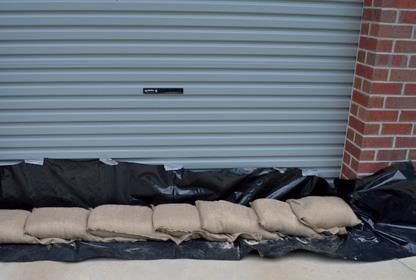 put plastic sheeting on the ground and overlap sandbags over the plastic sheeting