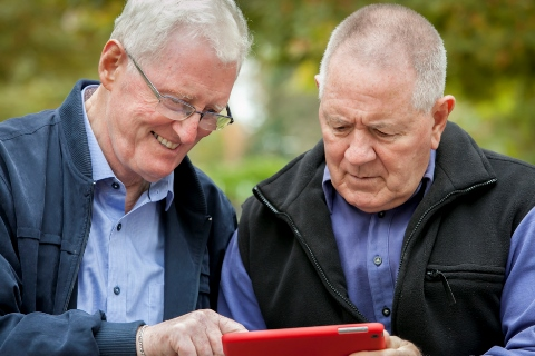 Senior man assisting another with digital technology